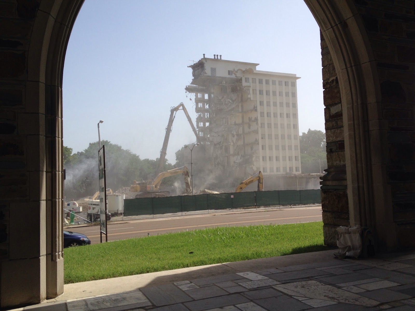 A Memphis building being destroyed viewed through an archway of a church.