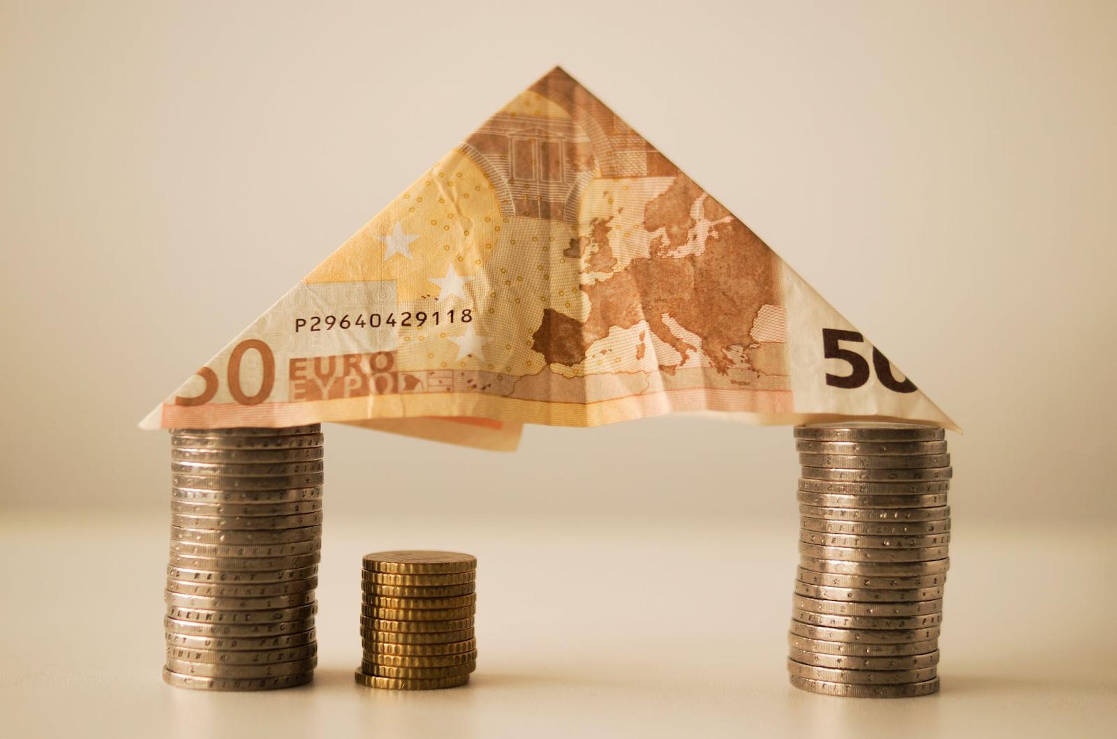 Diversas moedas empilhadas com uma nota de cinquenta euros em cima.