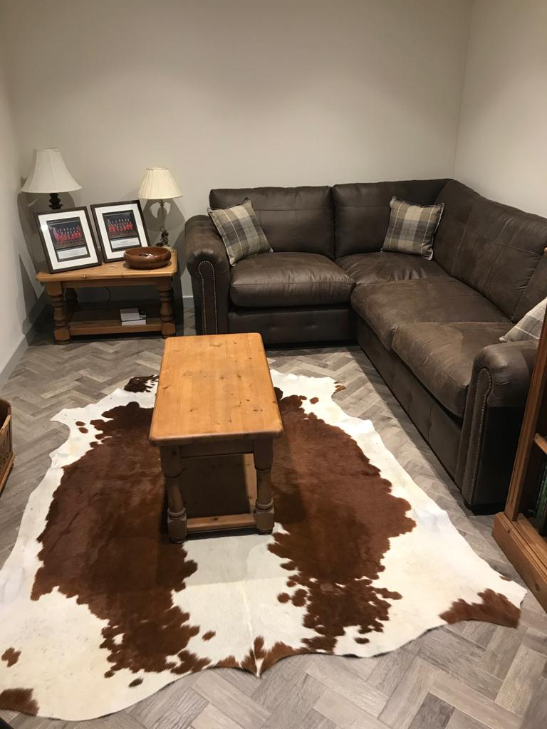 Brown and White cowhide rug in outside home office space next to furniture