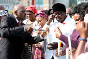 KwaZulu-Natal premier Willies Mchunu lights candles for the families who lost loved ones in the province during the recent floods.