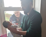Baby Faolán meets his grandfather through a window during social distancing in Ireland.