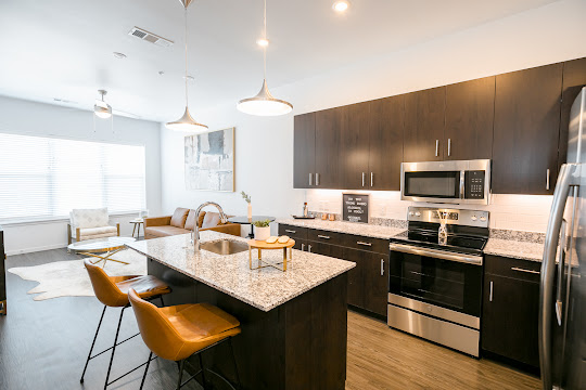 Kitchen with dark wood cabinets, white subway tile backsplash, and stainless steel appliances