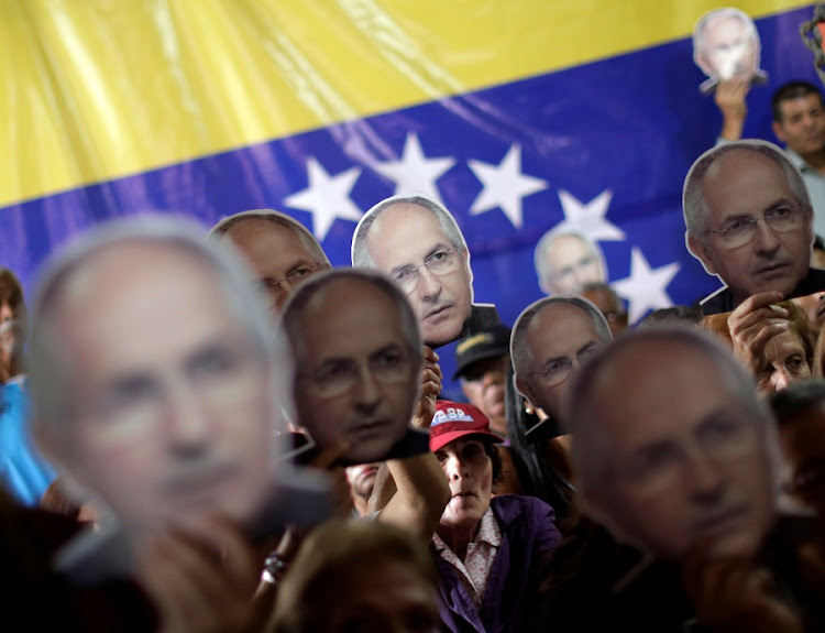 People hold portraits of opposition leader Antonio Ledezma during a news conference at the Venezuelan coalition of opposition parties headquarters in Caracas, Venezuela on August 1, 2017. Picture: REUTERS/UESLEI MARCELINO