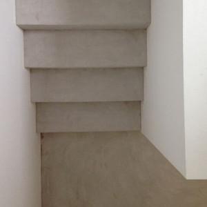 escalier en béton ciré avec palier en béton ciré créé une uniformité de coueleur à l'ecalier en enduit décoratif