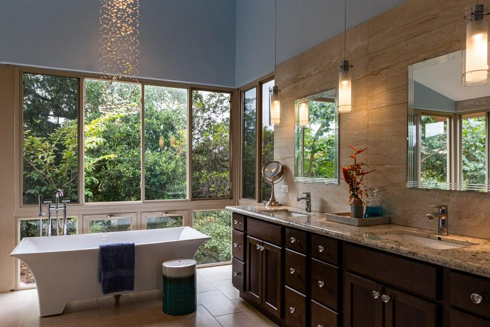 white freestanding bathtub and brown wooden cabinets