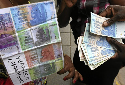 An illegal foreign currency trader counts notes at a local bus station in Zimbabwe's capital Harare in November 2016. Picture: REUTERS