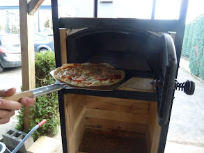 Photo: De oven bereikt makkelijk 300°C. De pizza wordt op de chamotte tegels gelegd en is na één a twee minuten gebakken. Er kunnen twee pizza tegelijk gebakken worden maar zo snel krijgen wij ze nog niet belegd!;)