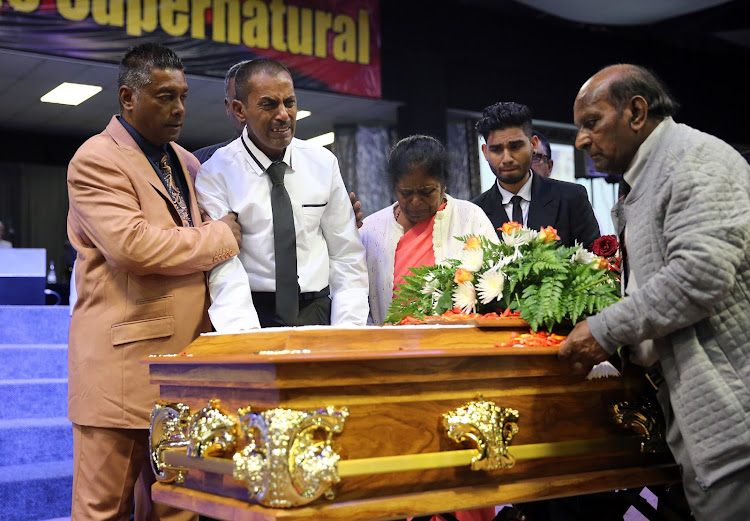 Father and husband Sagren Govindammy, in a white shirt and black tie, mourns as he pays his last respects to the triple murder victims, his wife Jane Govindsamy and his two daughters Denisha and Nikita as they are laid to rest after a funeral service held at the Faith Revival Centre in Durban yesterday