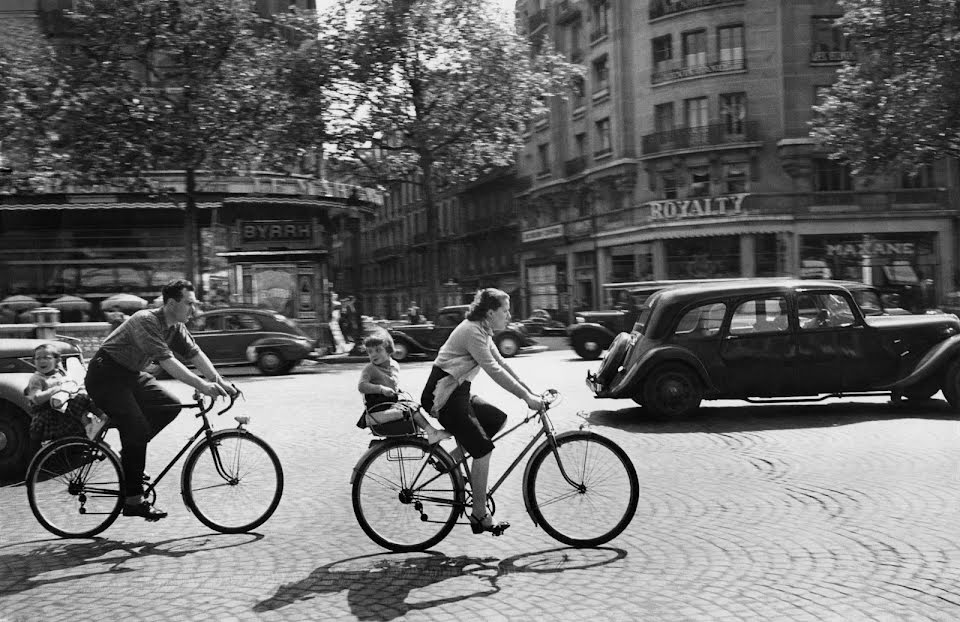 Photograph of a family of four riding bicycles through 1940s Paris near the Champs-Élysées