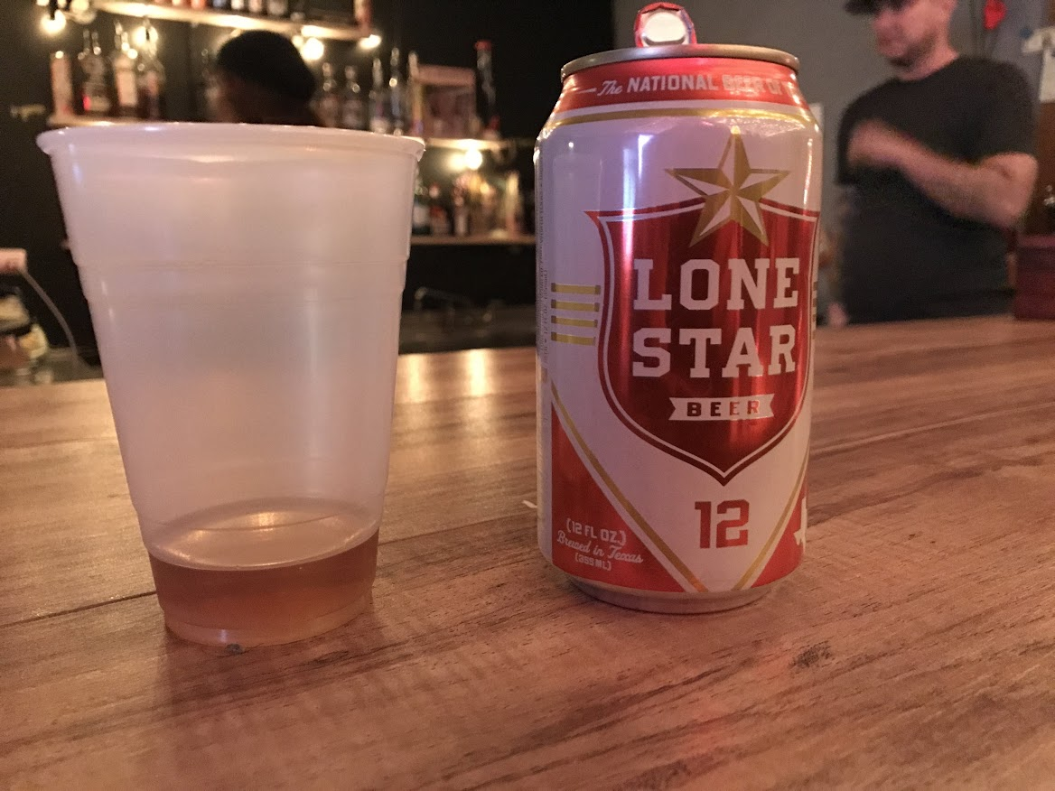 Shot of whiskey next to can of lone star beer