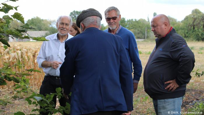 Слева направо: Ульрих, Иммо Гляйс и Алексей Савченко слушают местного жителя - он рассказывает, что слышал о похороненном в деревне офицере