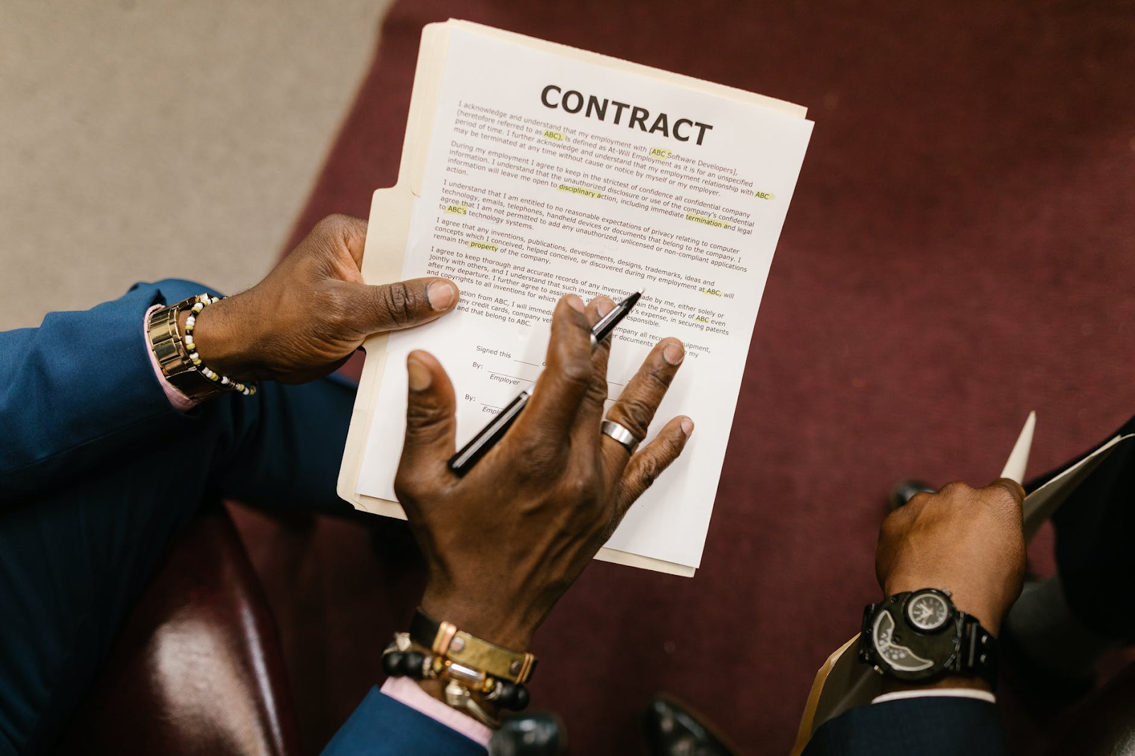 Person holding a contract and explaining the contents to another