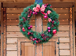 Photo: Christmas Wreath on natural wood doorway with strings of lights