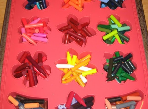 Fill the cavities of the silicone mold with crayon pieces.  Place the mold...