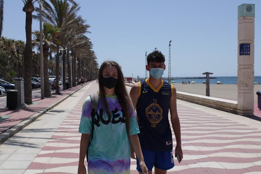 En pareja y con mascarillas por el Paseo Marítimo.