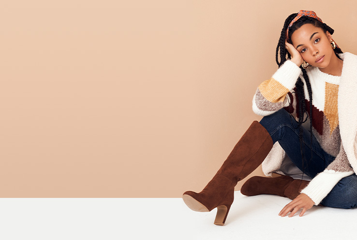 Woman sitting on the floor wearing a white block jumper, jeans and knee high brown boot heels