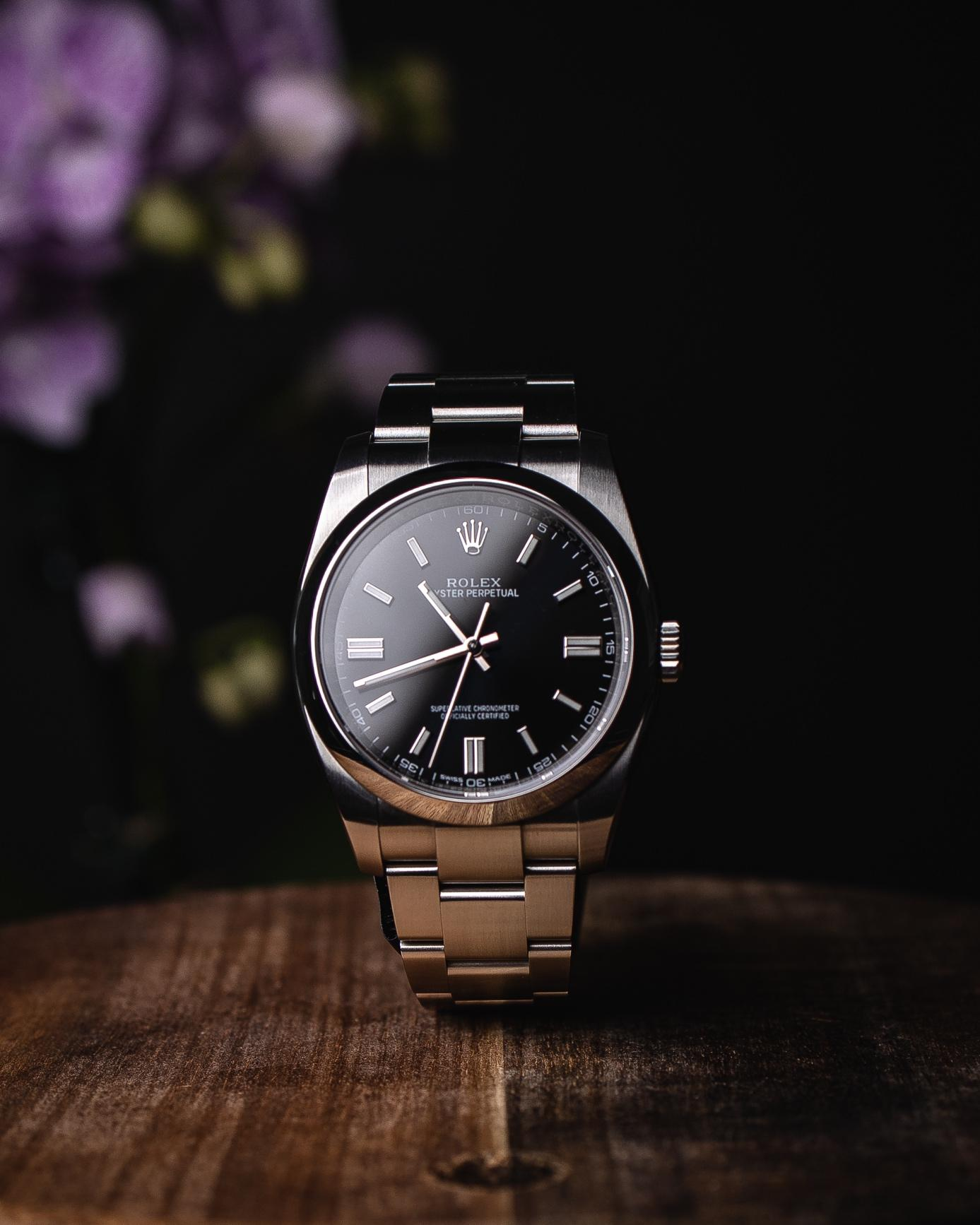 A watch on a wooden surface  Description automatically generated with medium confidence