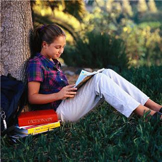 Girl reading magazine under tree