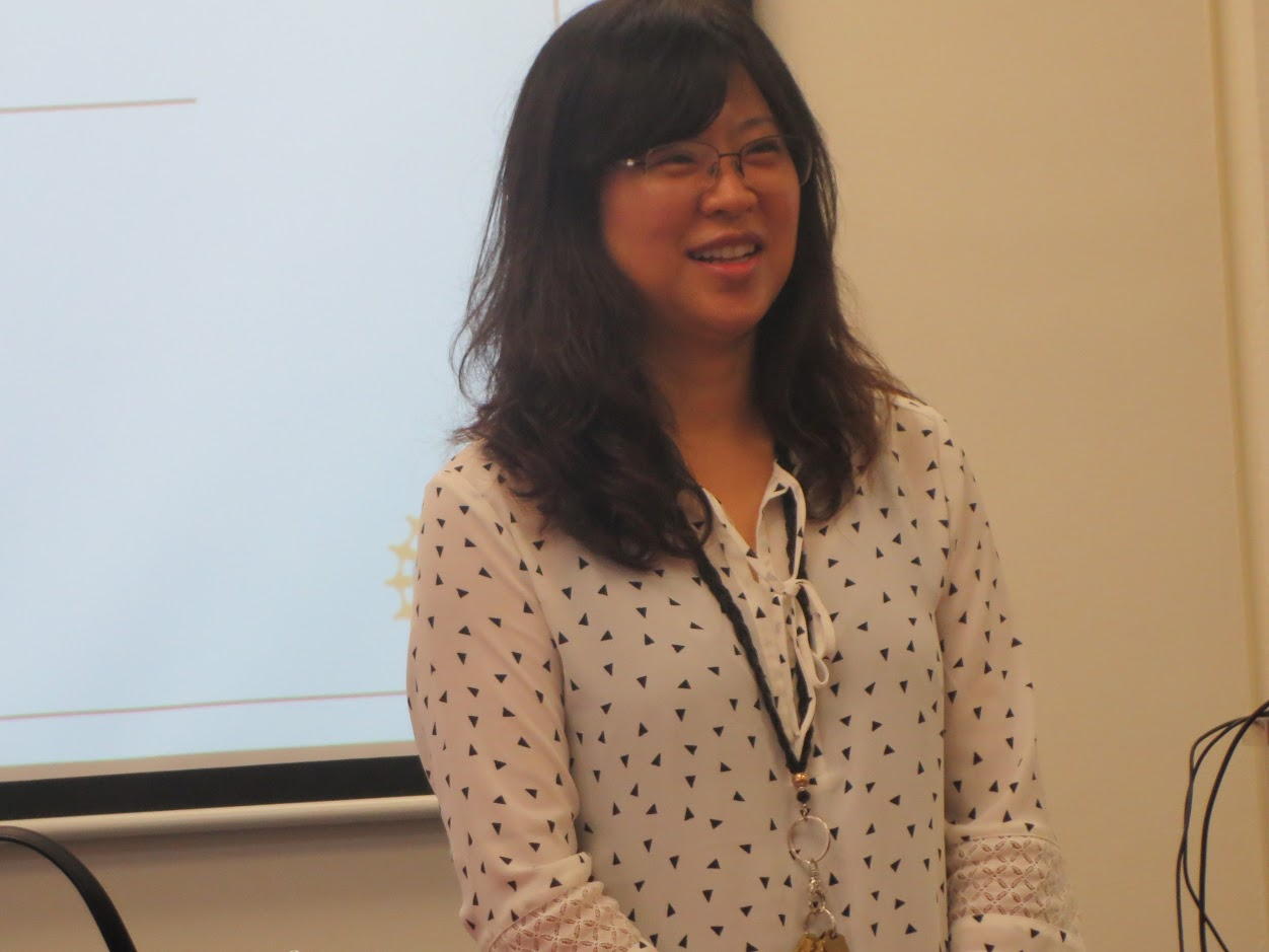 Dr. Elaine Kang in front of a projector screen