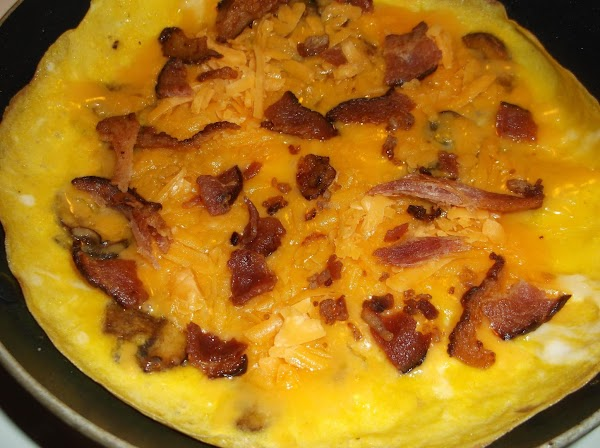 Lower heat to medium; sprinkle evenly with cheese and bacon.