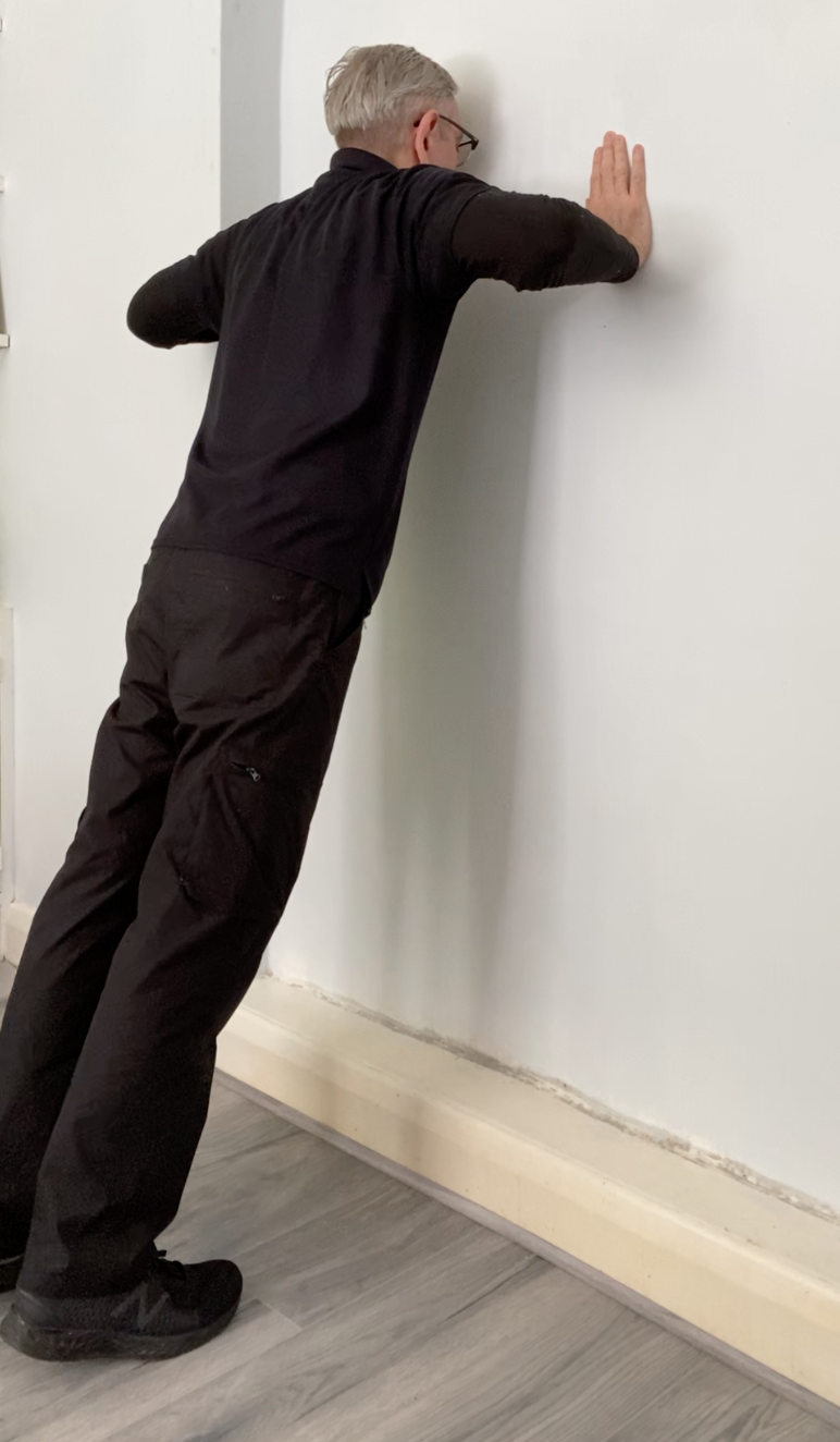 AB instructor Tony standing infront of a wall with his hands on the wall at chest height, shoulder width apart, with elbows bent and face near to the wall