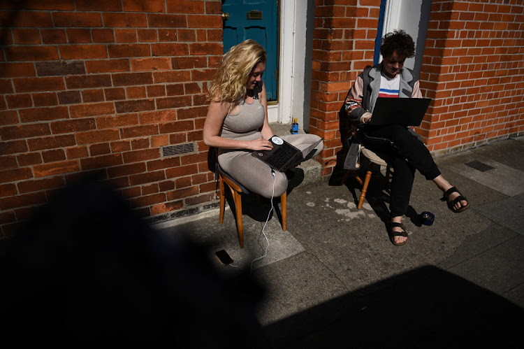 A man and woman work outside their doorsteps on laptops in sunshine, amid the coronavirus disease (Covid-19) pandemic, in Dublin, Ireland, April 3, 2021. Picture taken April 3, 2021.