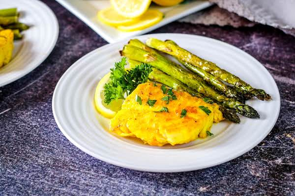 Turmeric Lemon Butter Basted Cod On A Plate With Asparagus.