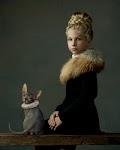 meisje met bonten kraag en kunstige gevlochten haren zit op tafel waarop een grijze poes met kanten kraag