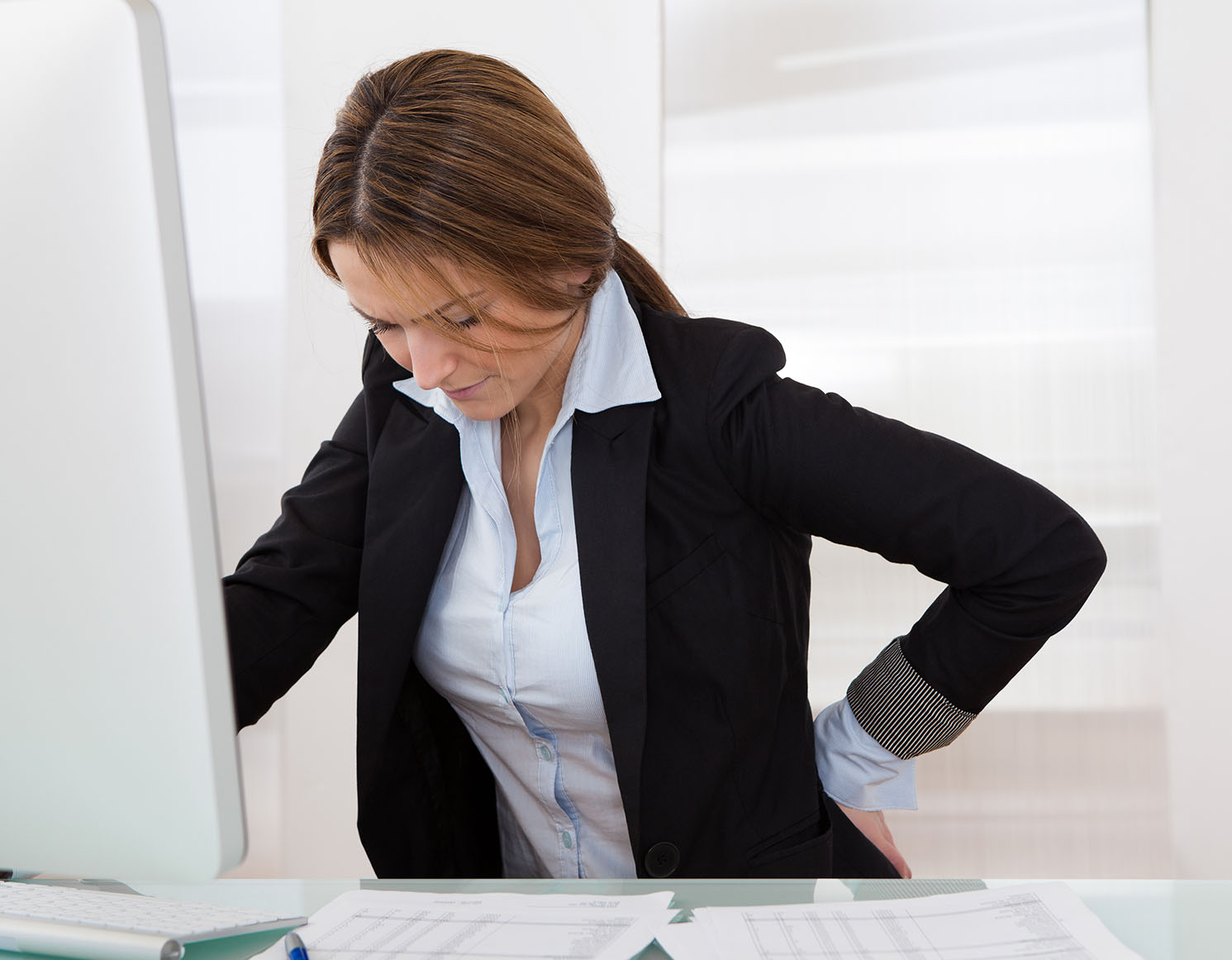 Woman with low back pain at work