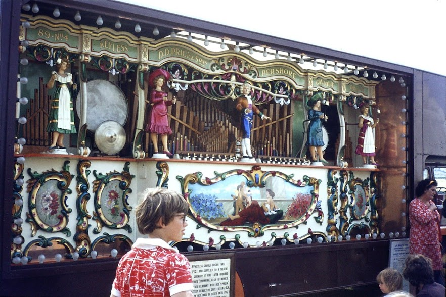 Boy not looking at fairground organ.