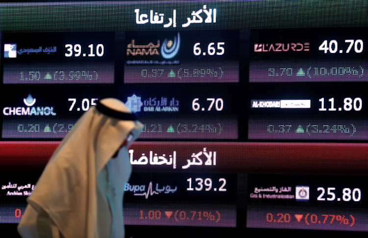 An investor walks past a screen displaying stock information at the Saudi Stock Exchange (Tadawul) in Riyadh, Saudi Arabia. Picture: REUTERS