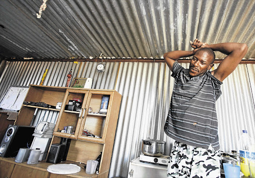 TEMPORARY ABODE: Sipho Ngubeni in a shack next to his demolished house in Lenasia Ext 13, south of Johannesburg. The Johannesburg council demolished houses it claimed were built on municipal land that was sold illegally