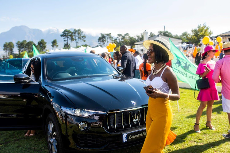 A guest dressed in Veuve Clicquot yellow walks in front of a Maserati Levant.