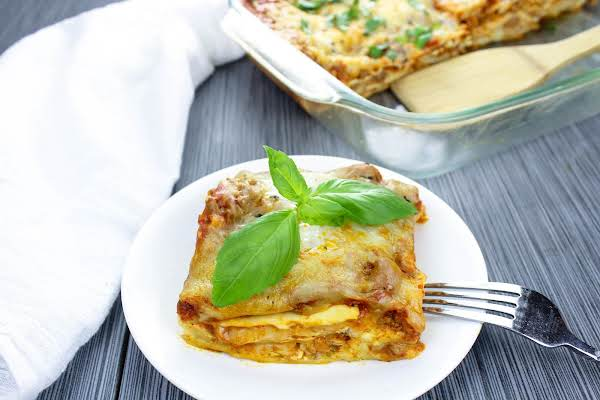 A Slice Of No Boil Lasagna On A Plate With Basil.