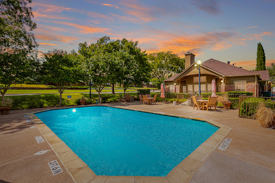 Wellington Place community pool with view of clubhouse in the background at dusk