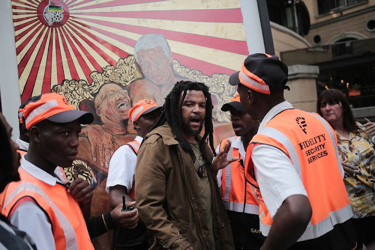 Controversial artist Ayanda Mabulu argues with security at Sandton Square in Johannesburg after erecting one of his artworks showing Jacob Zuma and Nelson Mandela in the shopping centre.
