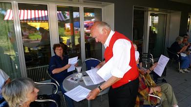 Photo: Zum Mitsingen werden Textblätter verteilt.