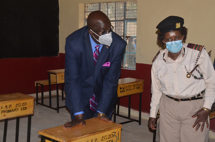 Education Cabinet Secretary George Magoha with Murang'a East Deputy County Commissioner Virginia Githumbi at Mjini primary school on Wednesday.