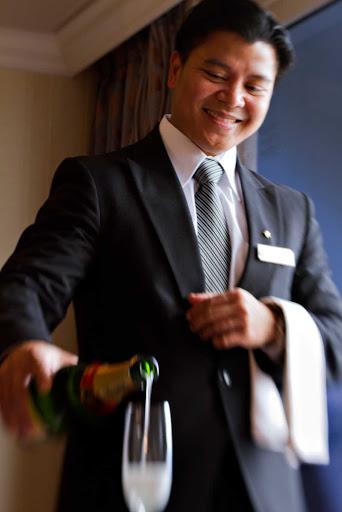 azamara-butler-champagne.jpg - A butler serves Champagne during an Azamara cruise.