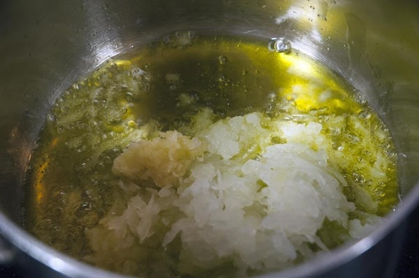 When the oil begins to shimmer, then add the onions, and garlic.