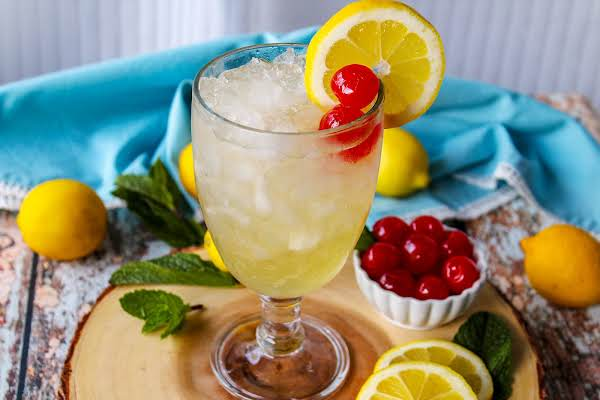Ingredients Poured Over Ice And Garnished With Lemon And Cherries.
