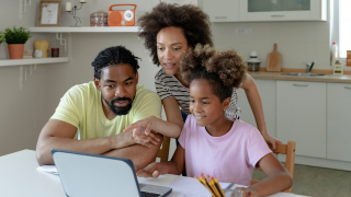 Un hombre, una mujer y una niña mirando un portátil