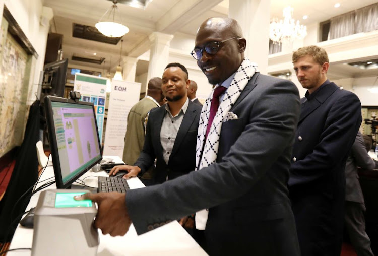 Home Affairs Minister Malusi Gigaba demonstrates how the new Automated Biometric Identification System will work in Cape Town on May 16, 2018.