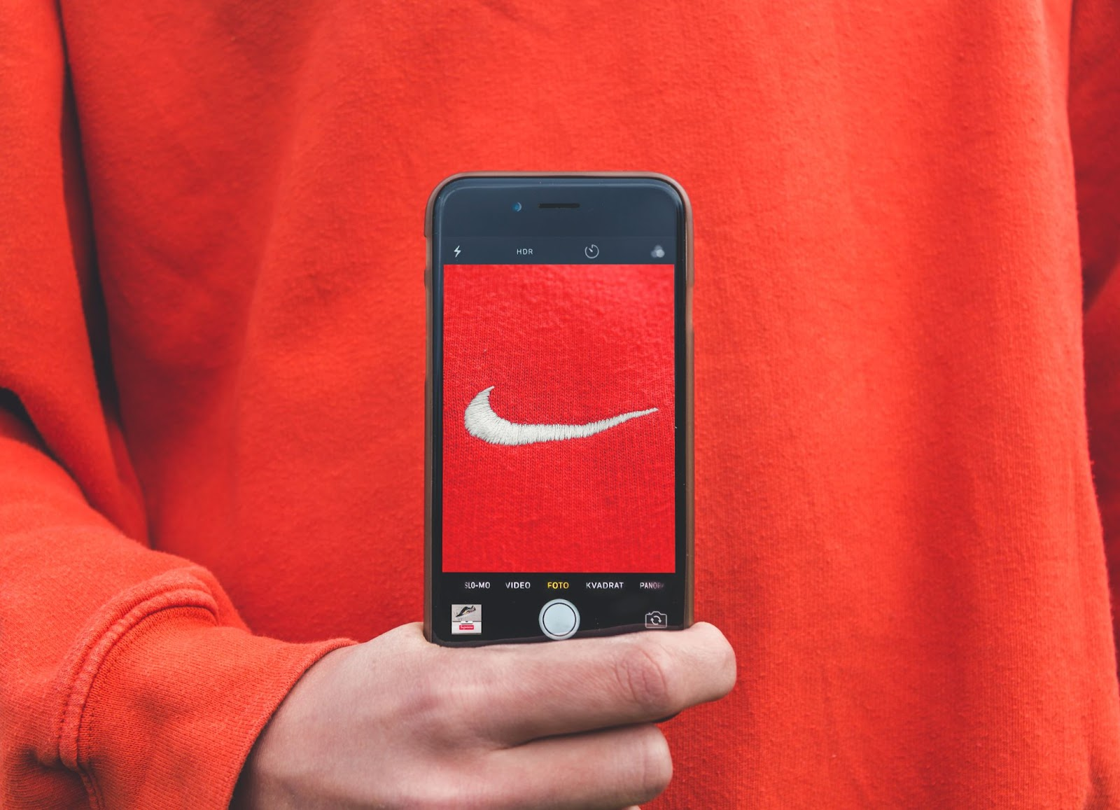 Nike swoosh logo in the center of a Iphone with the camera app open