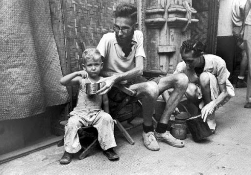 Emaciated father feeding army rations to his son