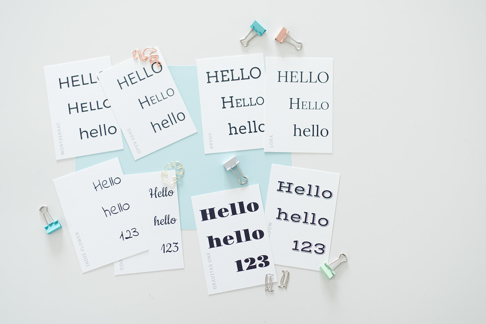 """The word """"hello"""" and """"123"""" printed on various pieces of paper. Each paper has the words printed in a different font types."""