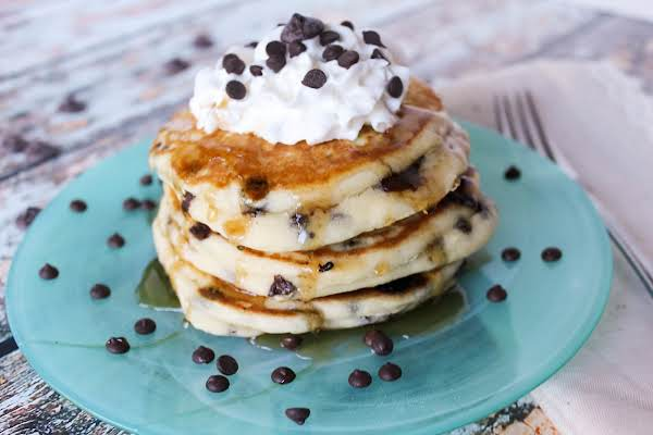 A Stack Of Chocolate Chip Pancakes With Whipped Cream, Maple Syrup, And More Chocolate Chips.