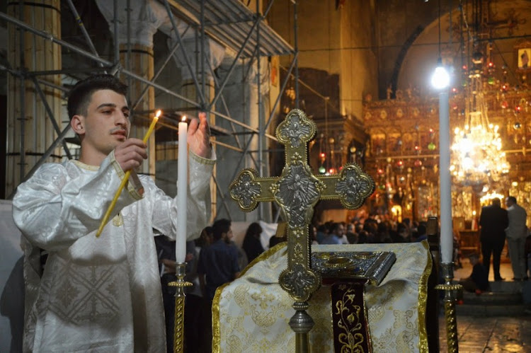 A Palestinian Christian lights candles in the Church of the Holy Sepulchre during Easter in Jerusalem. Although the Church is central to Jesus's death, crucifixion and resurrection, many Palestinians are barred from the Church by Israeli military
