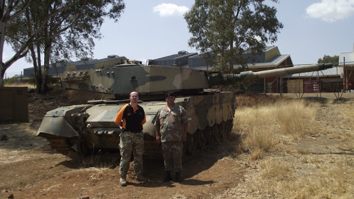 Dr Dewald Venter with the Chair of the SA Armour Museum Lt Col R Erasmus. In the background is a South African Olifant Mk1B Main Battle Tank.