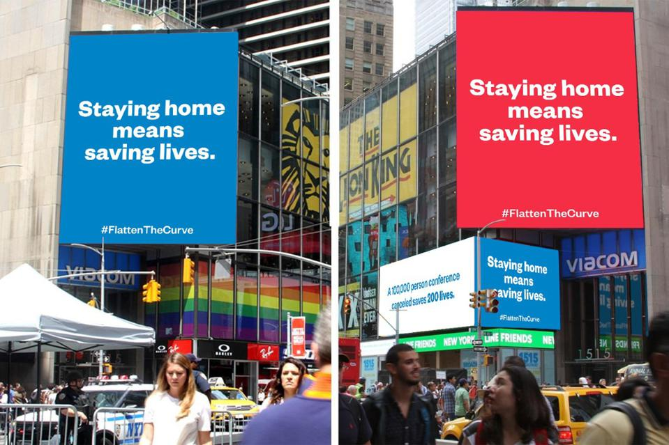 """Red and blue billboards in Times Square with the message """"Staying home means saving lives. #FlattenTheCurve""""."""
